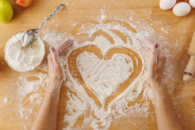 Ręcznie rysowane serce w mące na stole w kuchni i inne składniki. widok z góry.