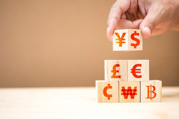 Ręcznie stawia drewniany sześcian znaku dolara amerykańskiego yuan yen euro i funt szterling.