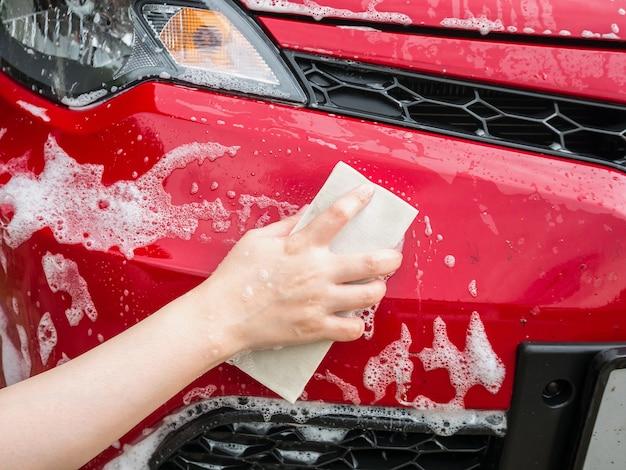 Ręcznie trzymaj gąbkę nad czerwonym samochodem do mycia