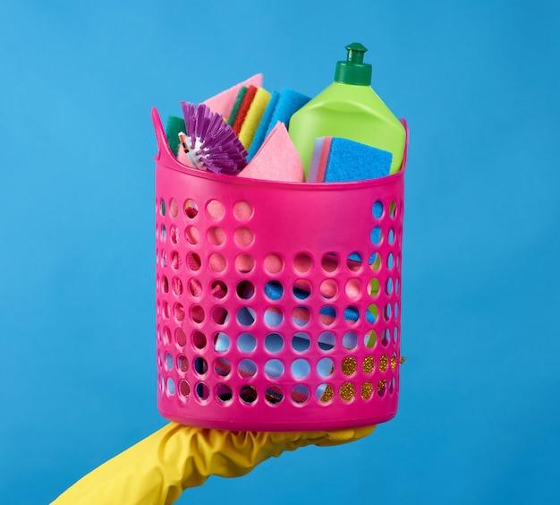 Ręcznie trzymaj różowy kosz z gąbkami do mycia, gumowymi rękawiczkami ochronnymi, szczotkami