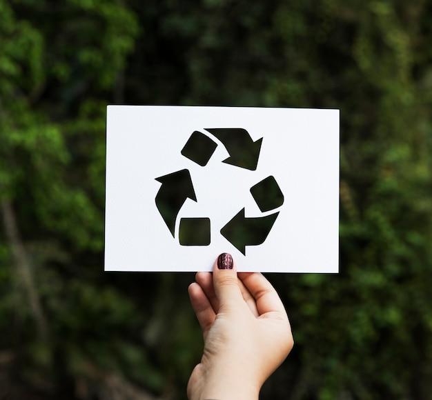 Ręcznie trzymaj znak recyklingu papieru rzeźba