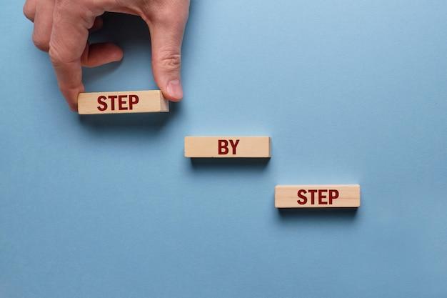 Ręcznie układa krok po kroku drewniane klocki z napisami.