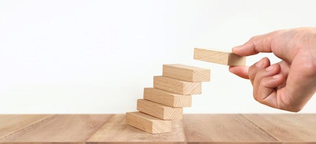 Ręcznie układanie bloków drewnianych jako schodki krok, proces wzrostu koncepcji biznesowej