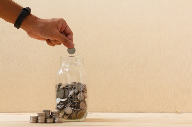 Ręcznie umieścić monetę do szklanej butelki. finanse, koncepcja gospodarki. koncepcja oszczędzania pieniędzy.