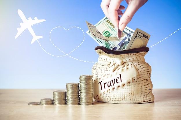 Ręcznie umieścić monetę w torbie z rachunkami w dolarach amerykańskich, monety stos na stole, rozmycie tła z sylwetką samolotu i poranne słońce świeci. koncepcja oszczędzania pieniędzy.