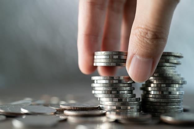 Ręcznie umieścić monety na stosie monet na białym tle, koncepcja inwestycji i oszczędzania.