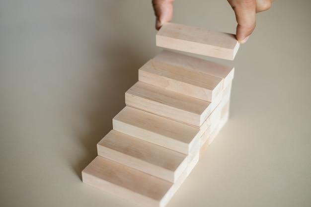 Ręcznie uporządkuj układanie drewnianych bloków jako schody schodkowe. koncepcja sukcesu procesu wzrostu biznesu