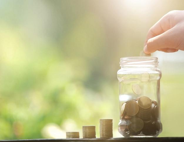 Ręcznie upuść pieniądze monety do słoika. oszczędność pieniędzy.