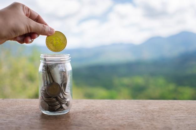 Ręcznie upuszczaj złoty bitcoin w słoiku pełnym monet i banknotów, co oznacza oszczędność inwestycji dzięki cyfrowej sieci kryptowalutowej sieci fintech. technologia biznesowa.