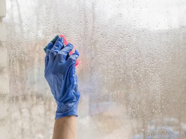 Ręcznie w rękawicach gumowych dezynfekuje okna środkiem dezynfekującym i gąbką