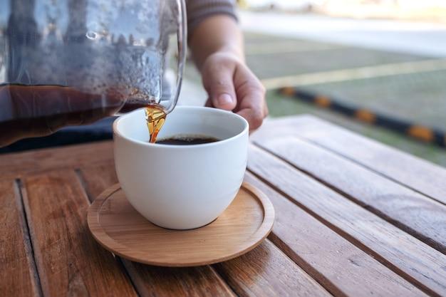 Ręcznie wlewając drip kawę do białego kubka na vintage drewnianym stole