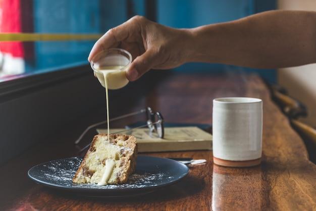 Ręcznie wlewając krem kremowy w ciasto owocowe z filiżanką kawy na stole.