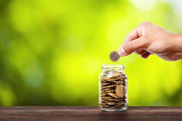 Ręcznie włóż monety pieniężne do szklanego słoika