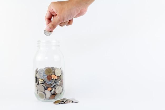 Ręcznie włożyć monetę do szklanej butelki. finanse, koncepcja gospodarki. koncepcja oszczędności pieniędzy.