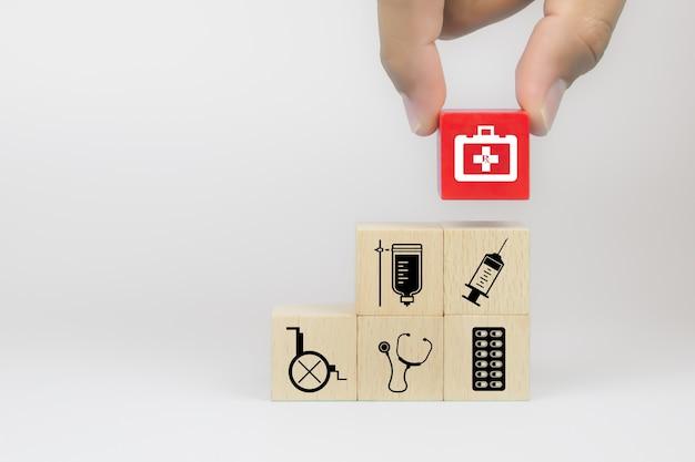 Ręcznie wybierz ikonę torby narzędzi medycznych na kostce drewniane klocki zabawki ułożone w stos z innymi symbolami medycznymi.