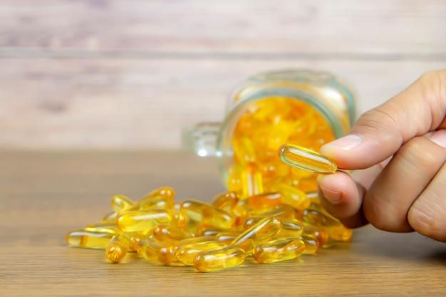 Ręcznie wybierz kapsułkę oleju z wątroby dorsza na stole.