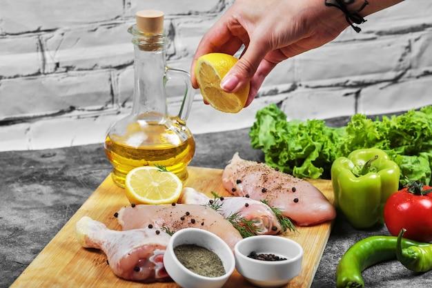 Ręcznie wyciskaj świeżą cytrynę na talerz surowych mięs z kurczaka z pęczkiem warzyw.