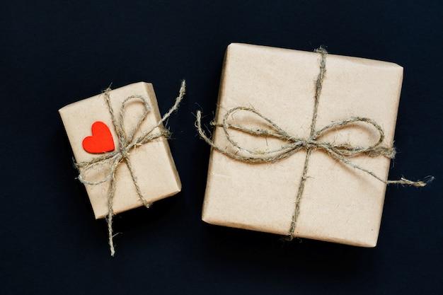 Ręcznie wykonane pudełko prezentowe owinięte papierem rzemieślniczym z czerwonym drewnianym sercem, liną i kokardą na czarnym tle