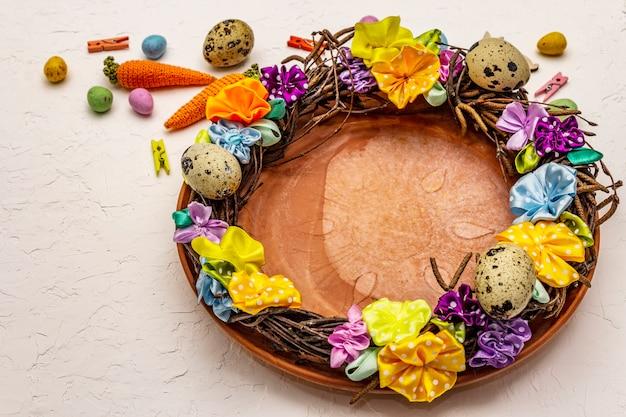 Ręcznie wykonany wielkanocny wieniec wiklinowy z jajkami przepiórczymi i ręcznie robionymi kwiatami