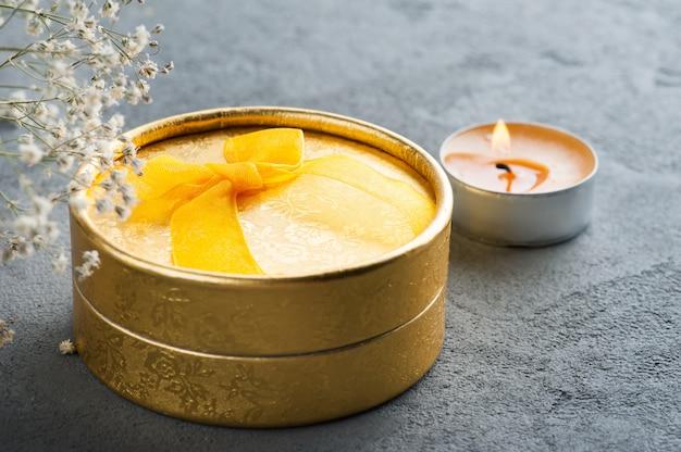 Ręcznie wykonany złoty prezent z kokardą, zapaloną świecą