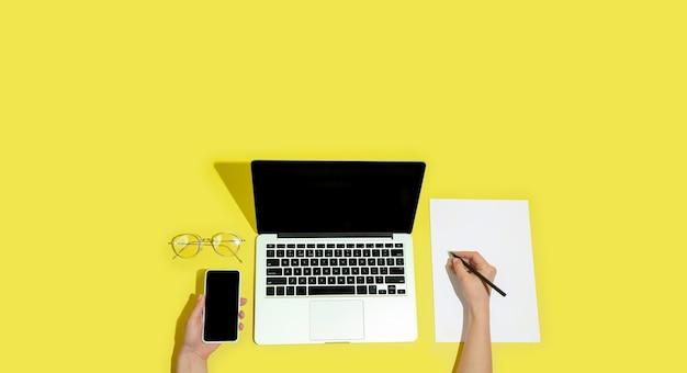 Ręcznie za pomocą gadżetów, urządzeń na żółtym tle widok z góry, pusty ekran z copyspace, minimalistyczny styl.