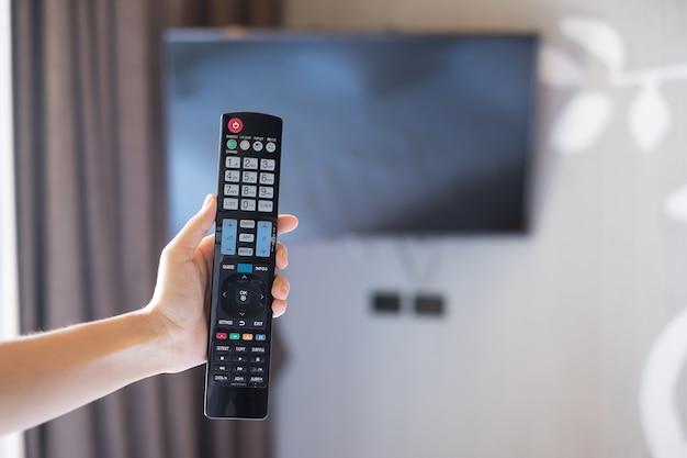 Ręcznie za pomocą pilota do regulacji smart tv w zamazanym pokoju hotelowym