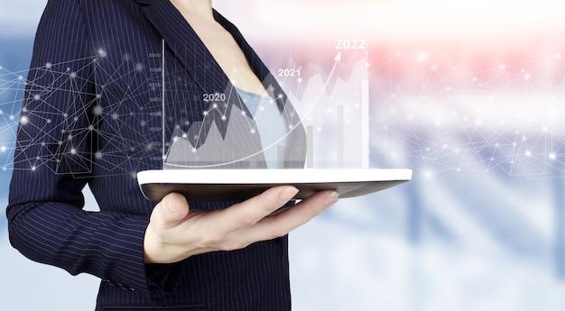 Ręcznie za pomocą tabletu analizując dane dotyczące sprzedaży i wykres wykresu wzrostu gospodarczego. ręka trzymać biały tablet z cyfrowym hologramem wykres wzrostu znak na jasnym tle niewyraźne. strategia biznesowa.