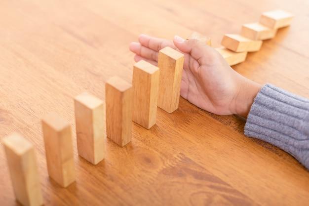 Ręcznie zatrzymaj drewniany blok, tworząc efekt domina
