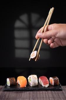 Ręcznie zbierając odmiany sushi pałeczkami na ciemnym tle. format pionowy.