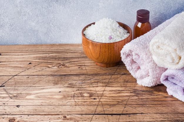 Ręcznik frotte i olejek kosmetyczny do masażu.