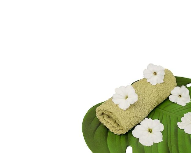 Ręcznik i kwiaty leżą na zielonym liściu. koncepcja spa, pielęgnacja ciała, pielęgnacja skóry dłoni. na białym tle na białym tle. skopiuj miejsce na tekst. kosmetyki naturalne, zabiegi upiększające