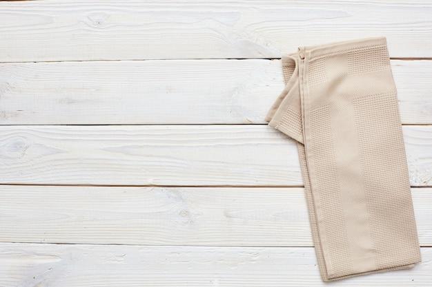 Ręcznik kuchenny beżowy na białym drewnianym. copyspace.