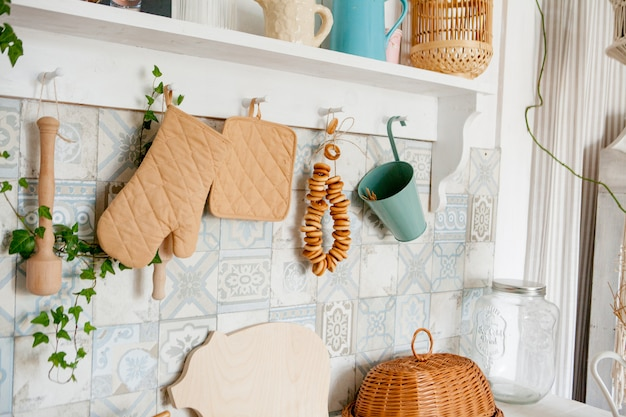 Ręcznik kuchenny i rękawica na blacie w nowoczesnej kuchni, akcesoria kuchenne wiszące w relingu dachowym na białej ścianie