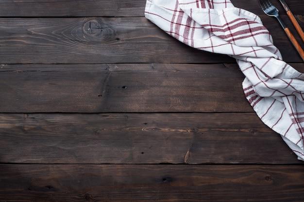 Ręcznik kuchenny serwetka tekstylna. drewniany stół rustykalny tło. skopiuj miejsce
