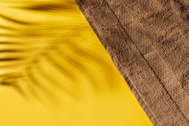 Ręcznik plażowy i cień tropikalnych liści na żółtym tle, kreatywne pastele, wakacje na plaży, koncepcja, miejsce na kopię, widok z góry
