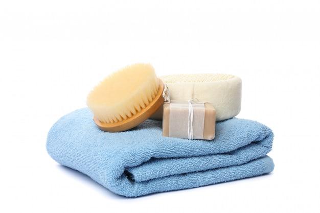 Ręcznik, szczotka, mydło i myjka na białym tle