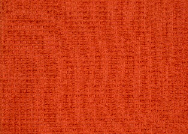 Ręcznik waflowy z pomarańczowej tkaniny we wzory wzór widoku z góry do projektowania lub tła.