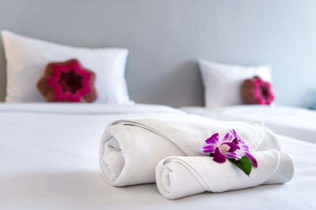 Ręcznik z orchideą na dekoracji łóżka w wnętrzu sypialni dla klienta hotelowego.