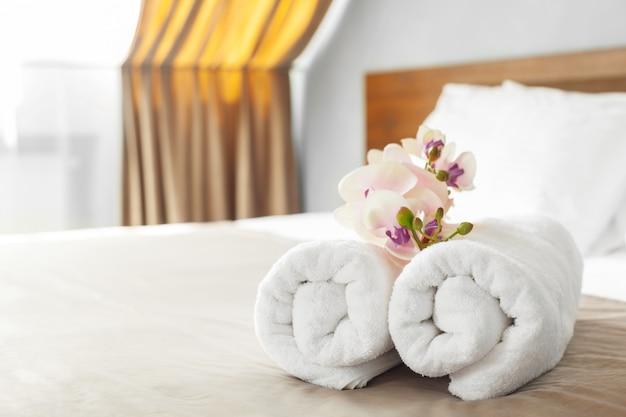 Ręczniki i kwiat na łóżku w pokoju hotelowym