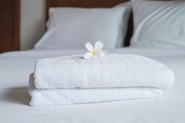 Ręczniki i plumeria na łóżku w luksusowym pokoju hotelowym gotowe do podróży turystycznej.