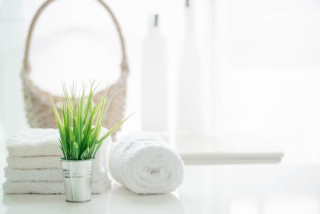 Ręczniki na białym stole z kopii przestrzenią na zamazanym łazienki tle