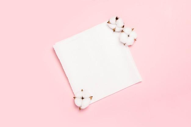Ręczniki papierowe i bawełniane kwiaty na różowej przestrzeni. concept to produkt w 100% naturalny, delikatny i miękki. widok płaski, widok z góry