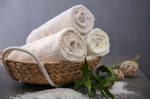 Ręczniki spa w wiklinowym koszu na ciemnej powierzchni