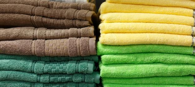 Ręczniki wielokolorowe w stosach na półce w sklepie, sekcja tekstylna w sklepie