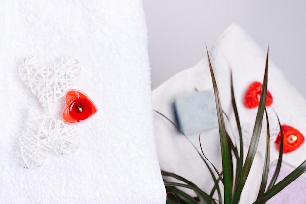 Ręczniki z serduszkiem i świecami zapachowymi oraz kwiatkiem do dekoracji. terapia uzdrowiskowa, koncepcja romantycznego relaksu. wysokiej jakości zdjęcie