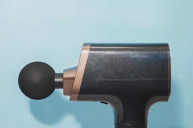 Ręczny bezprzewodowy profesjonalny pistolet do masażu szok terapeutycznego na niebieskim tle. masażer perkusyjny głębokich tkanek mięśniowych dla sportowców, odpręża, łagodzi ból. sport koncepcyjny i zdrowy styl życia
