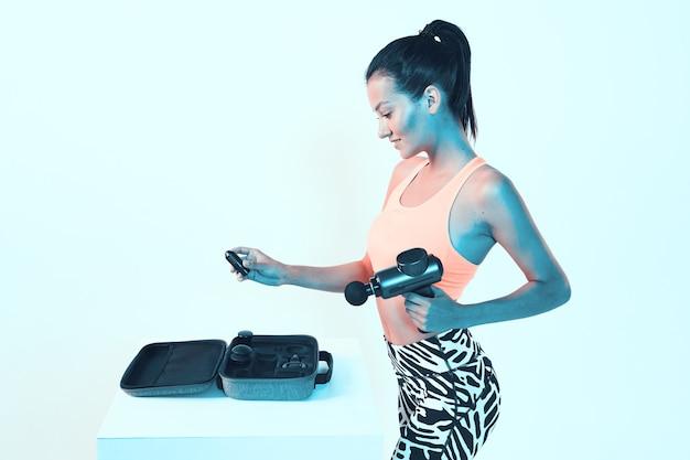 Ręczny masażer perkusyjny, wysportowana młoda dziewczyna wybiera w walizce przystawki do pistoletu do masażu