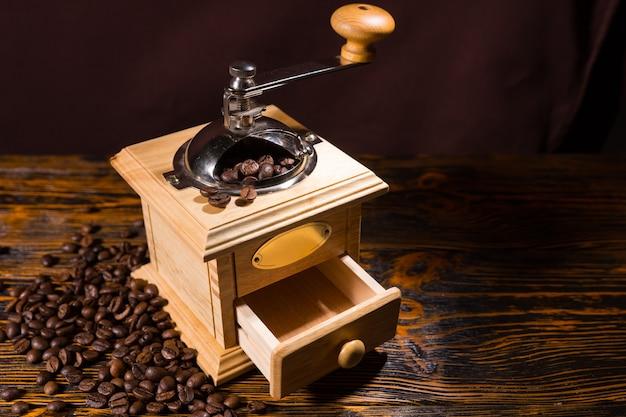 Ręczny młynek do kawy z porozrzucanymi ziarnami