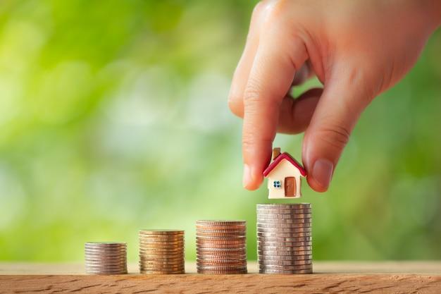 Ręczny model domu na stosach monet