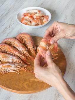 Ręczny obieranie krewetek. gotowane świeże gigantyczne krewetki, z bliska